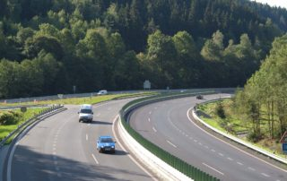 Dvouproudová silnice s projíždějícími auty - sjezd ve směru na Jablonec nad Nisou