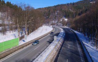Dvouproudová silnice v zimě s projíždějícími auty - příjezd do Jablonce nad Nisou