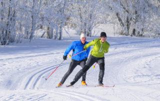 Dva běžkaři ve stopě v zasněžených Jizerských horách jedoucí volným stylem.