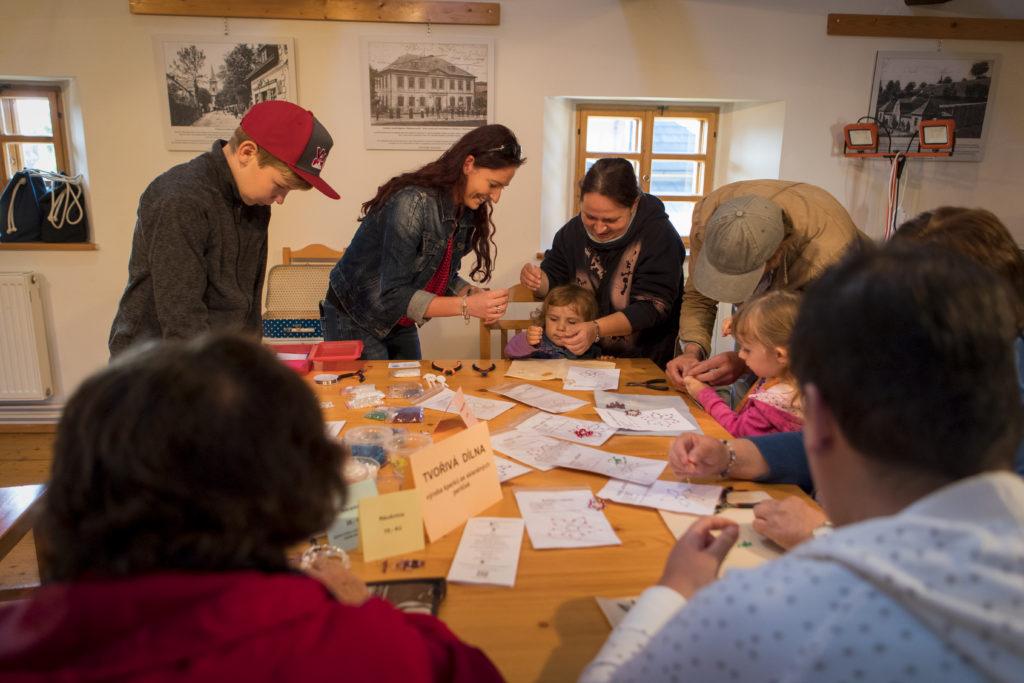 Lidé u stolu na korálkové dílně v Domě česko-německého porozumění v Rýnovicích - Jablonec nad Nisou