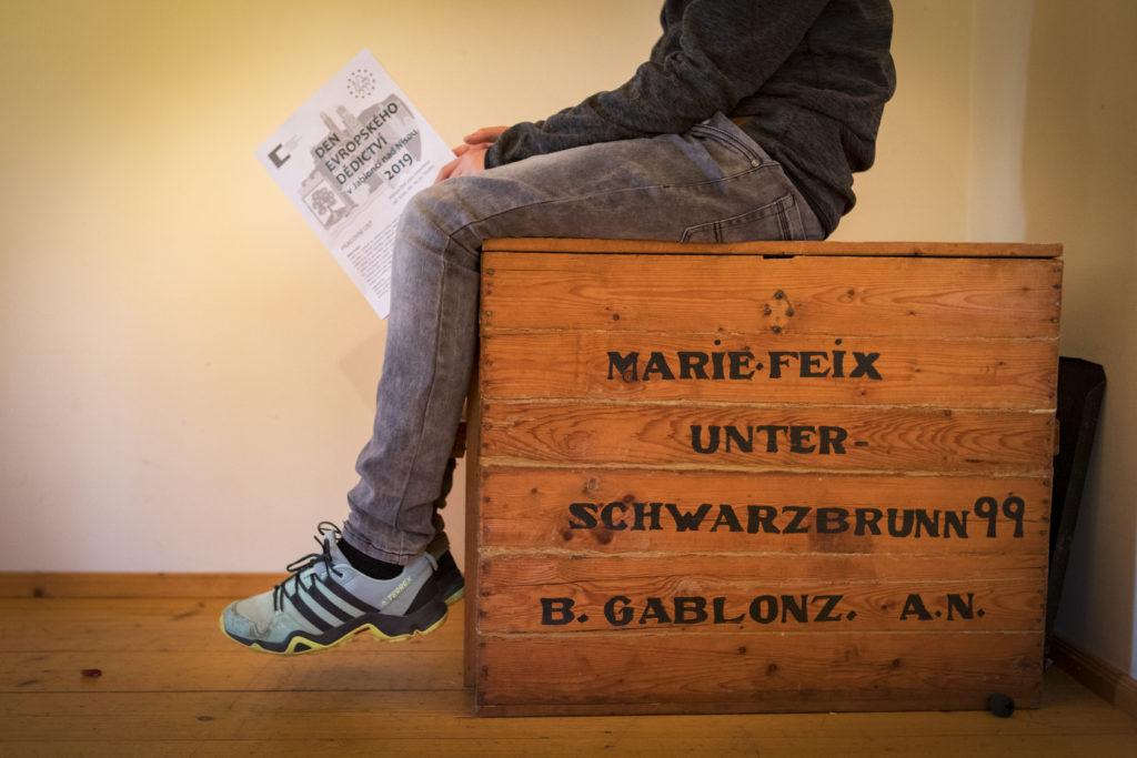 Chlapec sedící na dřevěné bedně s německými nápisy v Domě česko-německého porozumění v Rýnovicích - Jablonec nad Nisou