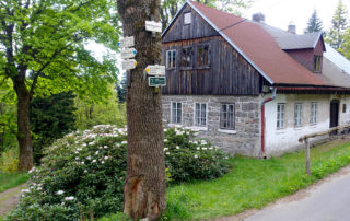 Částečně kamenná a dřevěná chalupa v Jizerských horách s turistickým rozcestím pod rozhlednou Královka