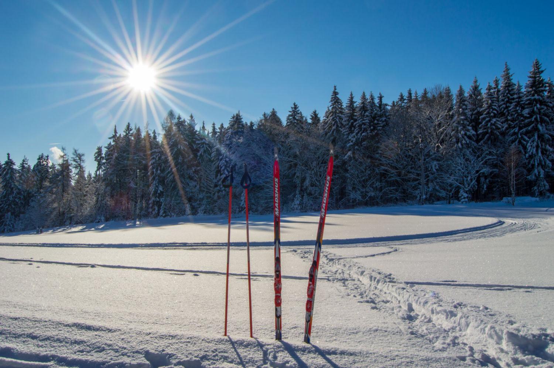 Zasněžená krajina, slunečný den a běžky zapíchnuté do sněhu – Jizerské hory