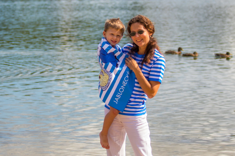 Maminka v pruhovaném tričku držící dítě v ručníku na břehu jablonecké přehrady Mšeno