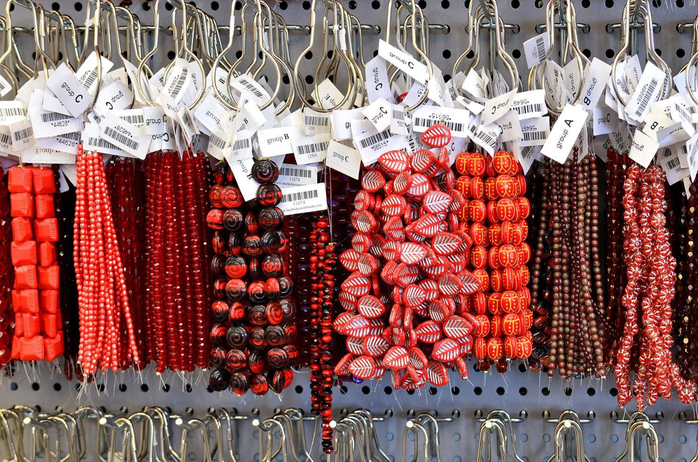 Červené náhrdelníky ze skleněné bižuterie visící v obchodě GB beads
