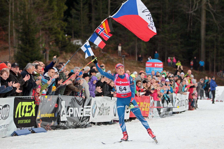Biatlonistka Gabriela Koukalová v Jablonci nad Nisou při biatlonové exhibici na závěr sezóny s českou vlajkou v ruce a fanoušky v pozadí.
