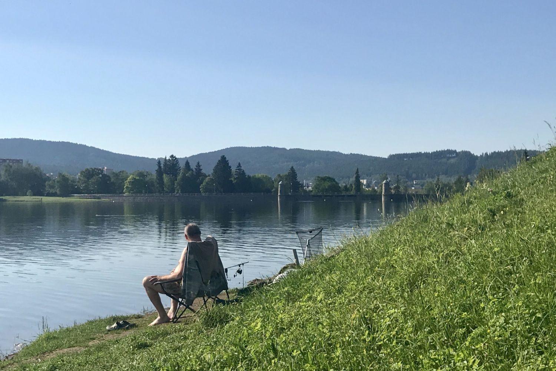 Rybář sedící zády u vody na břehu jablonecké přehrady s hrází v pozadí.