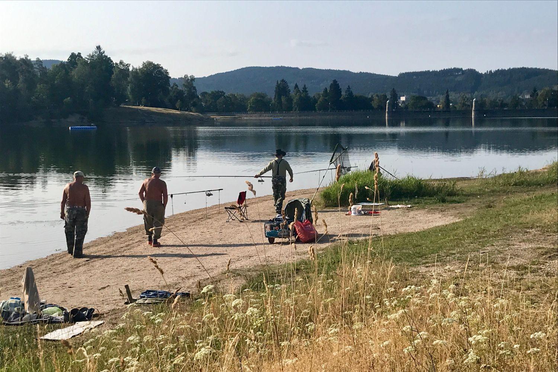Skupinka rybářů na břehu jablonecké přehrady s rybářským náčiním.