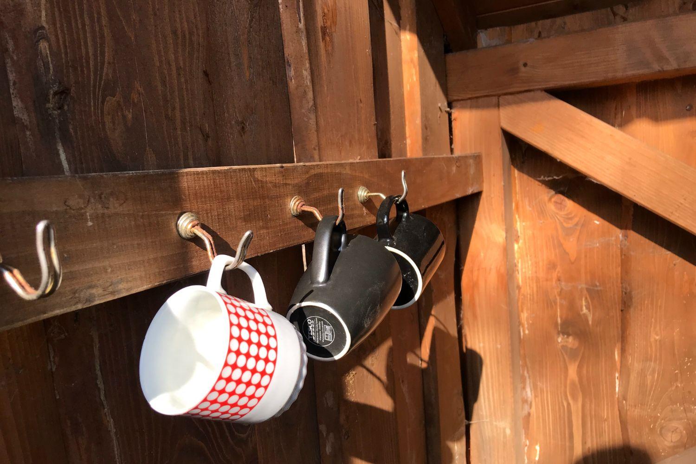 Hrnečky visící na dřevěné stěně u studánky v Jindřichově - Jizerské hory