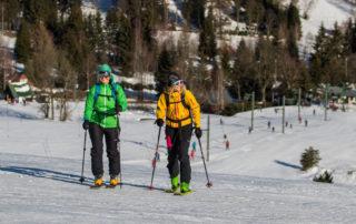Dvě lyžařky v menším skiareálu stoupající po sjezdovce - Jablonecko