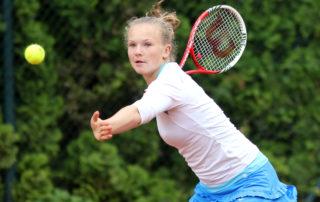 Dívka s napřáženou rukou držící raketu a  hrající tenis