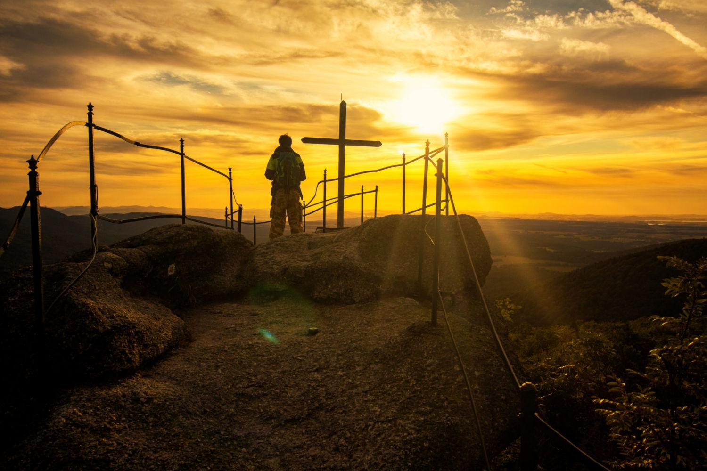 Turista na skalní vyhlídce Paličník s křížem při západu slunce – Jizerské hory
