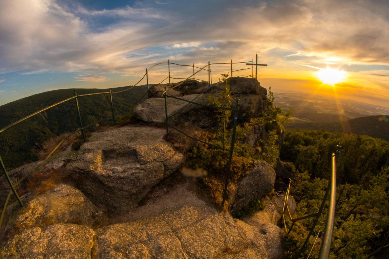 Skalní vyhlídka Paličník s křížem a kovovým zábradlím při západu slunce – Jizerské hory