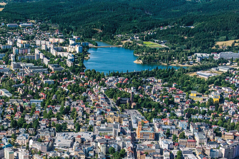 Letecký pohled na zelený Jablonec nad Nisou s přehradou uprostřed