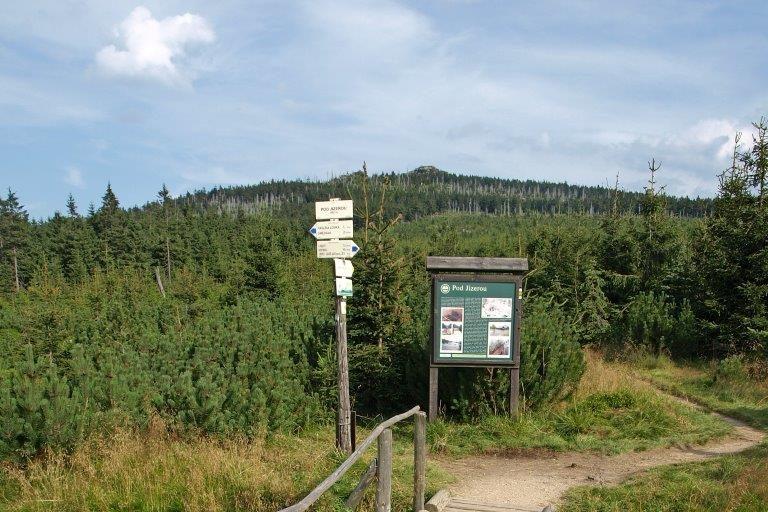 Turistické rozcestí a dřevěný chodníček v Jizerských horách pod vrcholem Jizery.