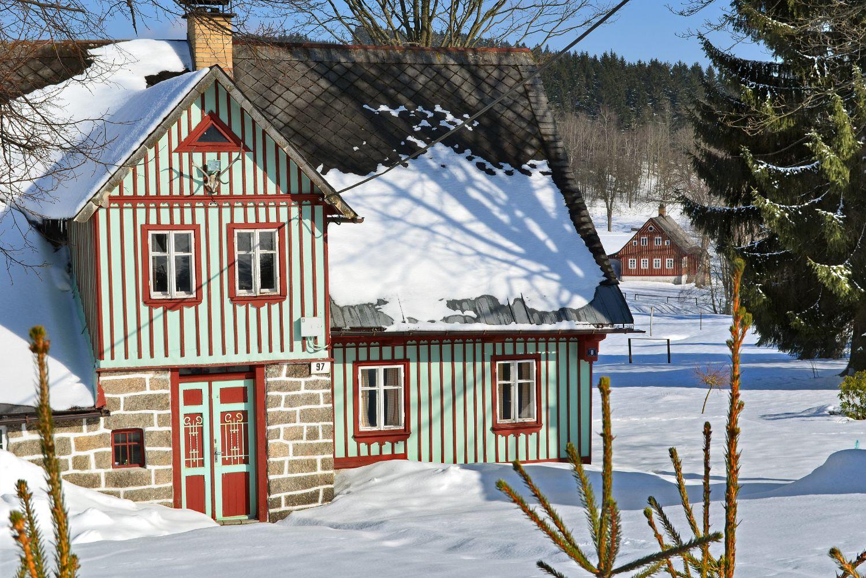 Dřevěná chalupa v Jizerských horách (Karlov) v zimě - roubení v zeleno-červeno-bílé barvě