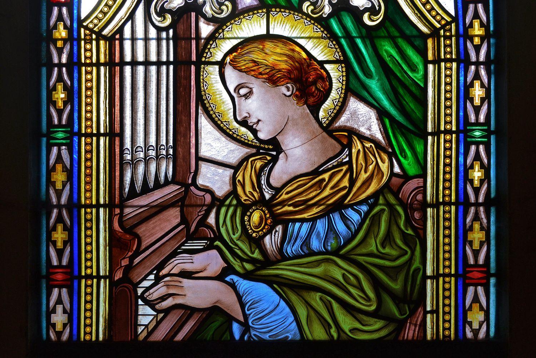Barevná vitráž se zobrazení ženy se svatozáří hrající na varhany