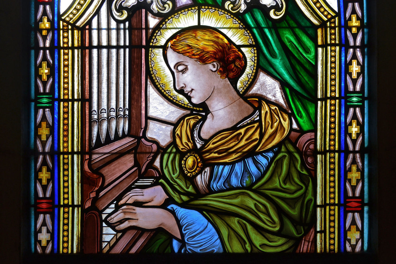 Barevná vitráž se zobrazení ženy se svatozáří hrající na varhany - kostel Nejsvětější Trojice, Mšeno, Jablonec nad Nisou
