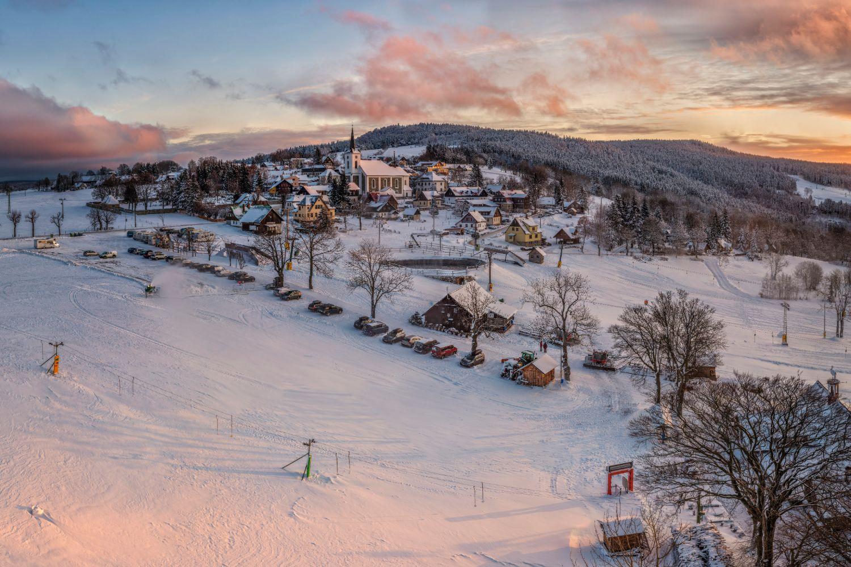 Letecký pohled na Příchovice na pomezí Jizerských hor a Krkonoš v zimě při západu slunce