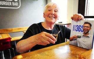starší usmívající se žena držící v ruce knihu