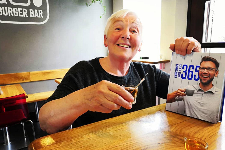 starší usmívající se žena držící v ruce knihu 365 Gastromapa Lukáše Hejlíka u stolu v restauraci Q Burger bar v Jablonci nad Nisou
