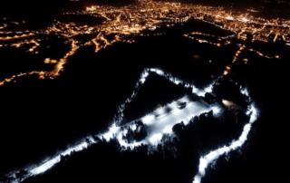 Letecký večerní snímek svítícího běžkařského areálu Kolečko – Jablonec nad Nisou Břízky v zimě