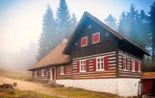Roubená Liščí bouda s expozicí sklářství na Kristiánově v Jizerských horách částečně v mlze