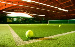 Tenisový míček ležící na umělém povrchu v tenisové hale Hotelu Břízky v Jablonci nad Nisou