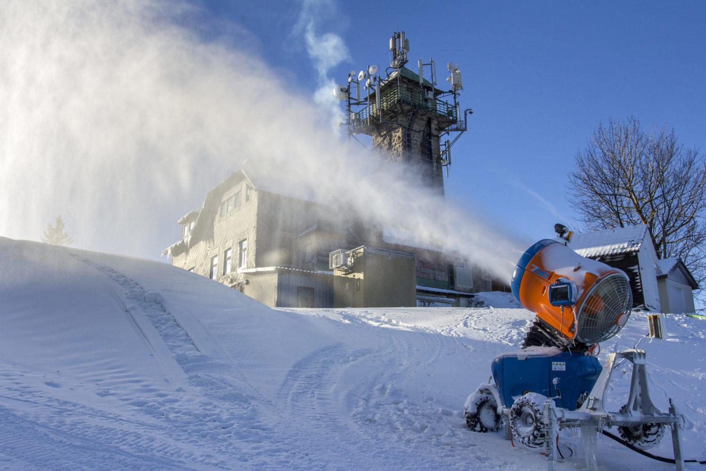 Sněžné dělo zasněžuje sjezdovku Tanvaldský Špičák (Skiaréna Jizerky). V pozadí restaurace s rozhlednou.