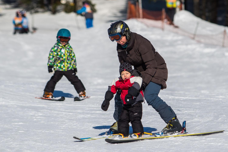 Maminka učící malého lyžaře na sjezdovkách