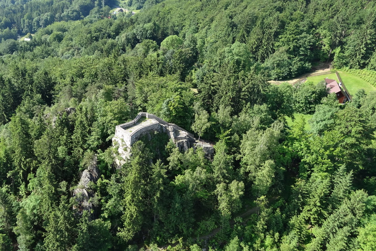Skalní vyhlídka Terezínka na úbočí zalesněného vrcholu Muchov, jenž se zvedá nad městem Tanvald - letecký pohled