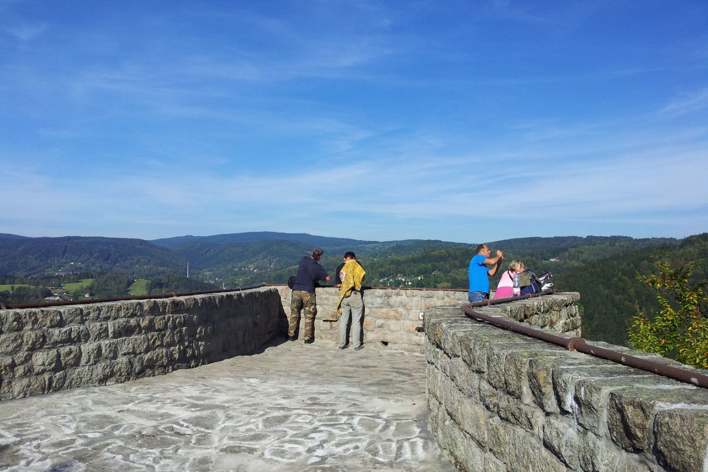 Turisté na kamenné terase skalní vyhlídky Terezínka nad městem Tanvald.