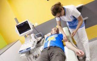 Pacient ležící na lůžku v nemocnici při vyšetření v Jablonci nad Nisou. Zdravotní sestřička se chystá mu odebrat krev. Ambulance se postará v případě potřeby i o turisty.