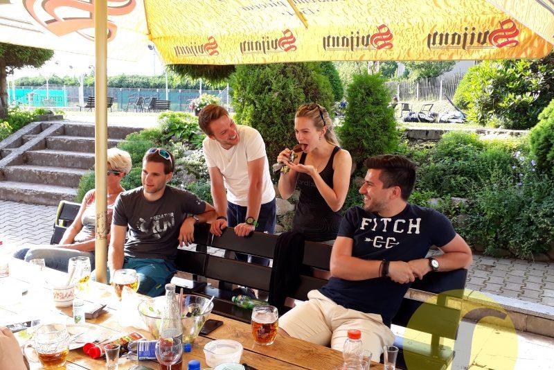parta mladých sportovců po tenisovém zápase relaxující a občerstvující se u stolu  na terase - kurty
