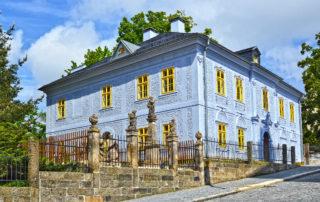 Dům národopisců Jany a Josefa V. Scheybalových v Jablonci nad Nisou - bývalá fara kostela sv. Anny s obnovenou fasádou ve světle modré barvě - vpopředí Getsemanská zahrada