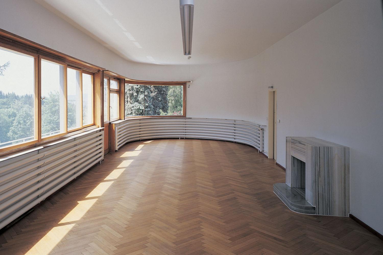 Funkcionalistická Háskova vila v Jablonci nad Nisou - pohled do interiéru - zaoblená místnost s velkými okny, parketami a krbem