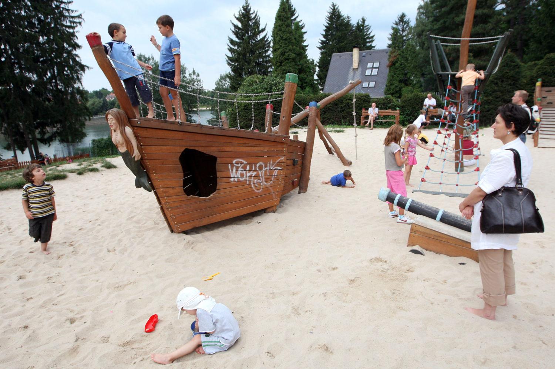 Dřevěná prolézačka ve tvaru lodě, písek a hrající si děti na dětském hřišti u přehrady v Jablonci nad Nisou - Mšeno