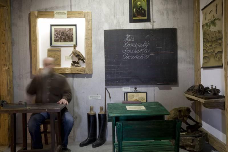 Interiér Muzea cimrmanovy doby - lavice, školní tabule a postava