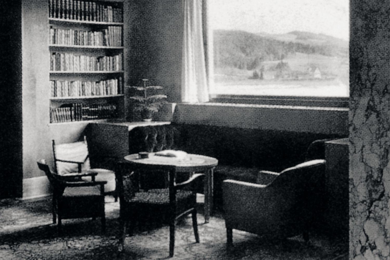 Funkcionalistická Kantorova vila v Jablonci nad Nisou – dobové foto interiéru (křesílka, stolek, knihovna a velké okno s výhledem na přehradu)