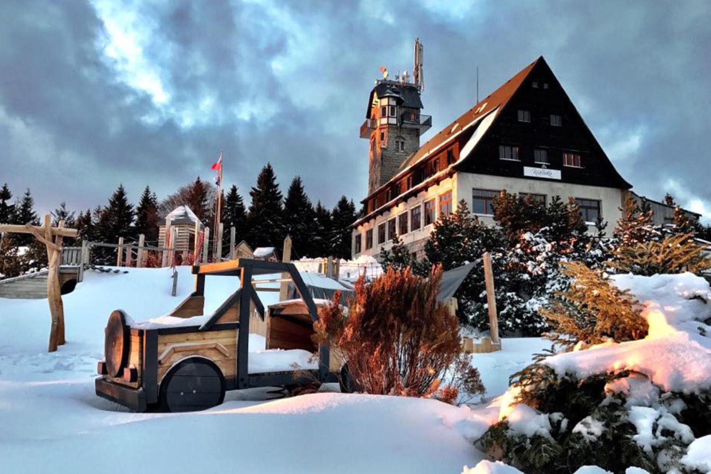 Hotel a rozhledna Královka v Jizerských horách v zimě. V popředí dětské hřiště.
