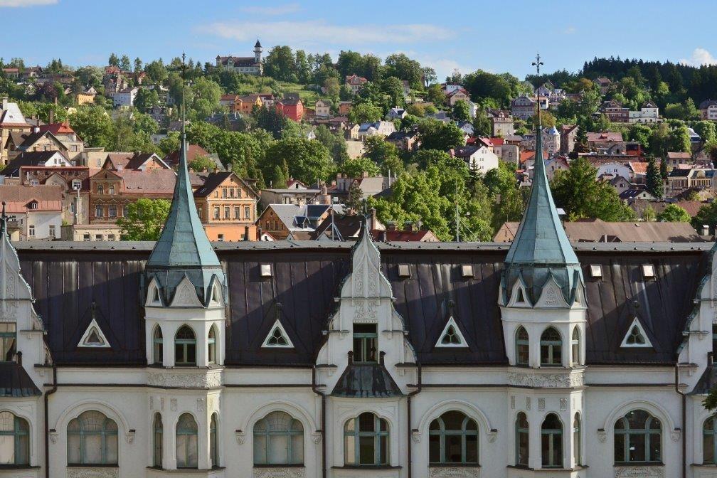 střešní část secesní budovy Mzea skla a bižuterie v pozadí Jablonec nad Nisou – starší zástavba v kopci směrem na Petřín
