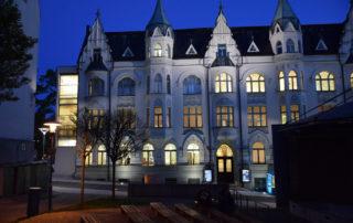 Secesní budova Muzea skla a bižuterie Jablonci nad Nisou v noci s rozsvícenými okny - pohled zvenčí