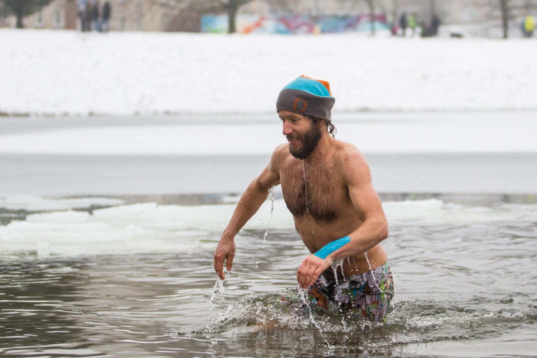 Otužilec v plavkách v zimě vstupující do ledové vody v jablonecké přehradě Mšeno v průběhu závodu Iceman