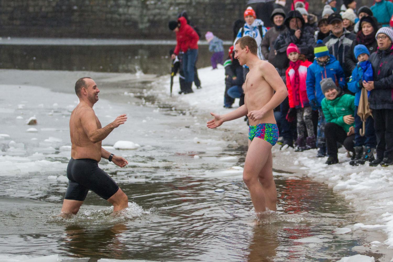 Dva otužilci v plavkách v zimě vstupující do ledové vody v jablonecké přehradě Mšeno v průběhu závodu Iceman. Na břehu přihlížejí diváci v bundách.