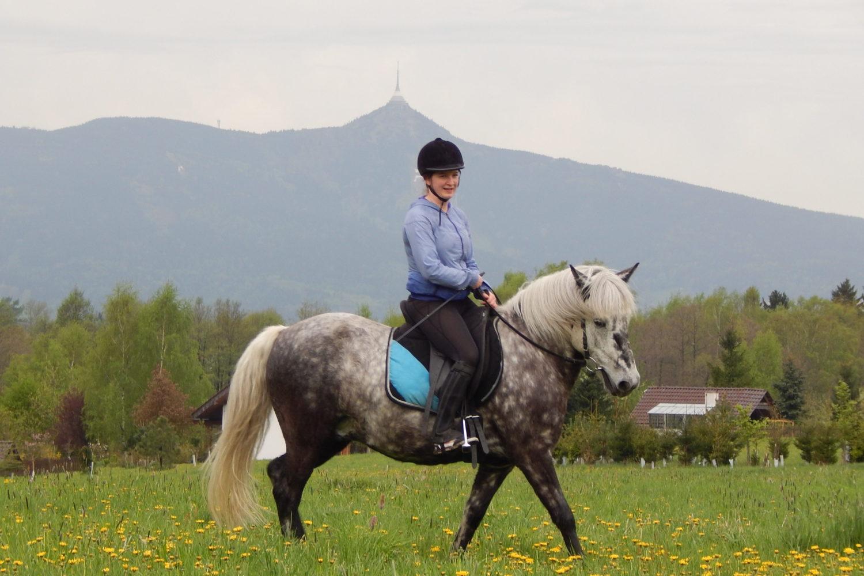 Dívka jedoucí na poníku - v pozadí Ještěd