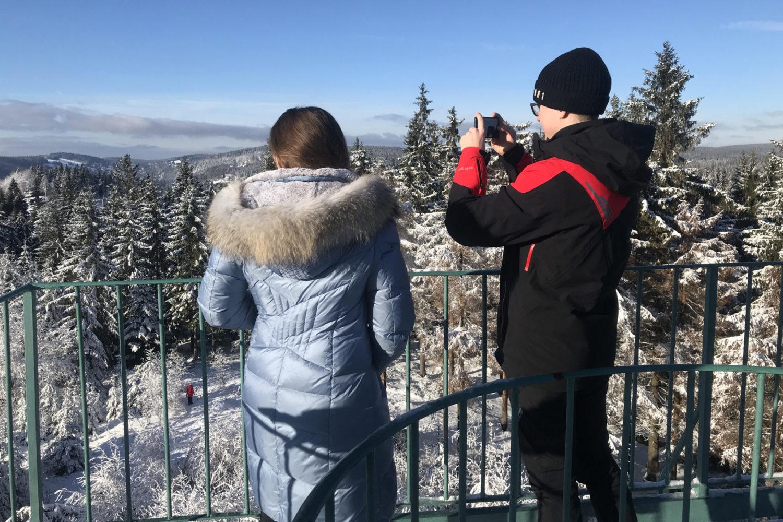 Dvojice turistů fotící si zasněženou krajinu Jizerských hor z rozhledny Slovanka