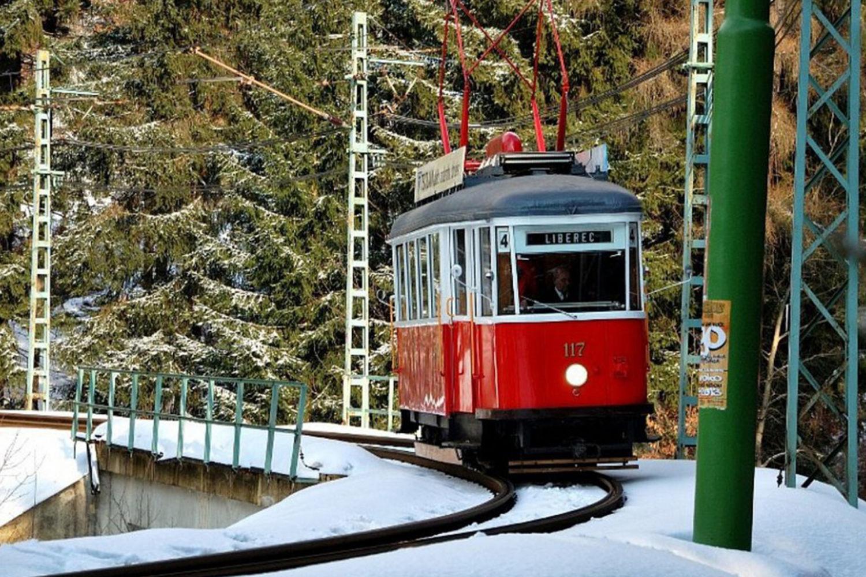 Historická tramvaj Liberec-Jablonec jedoucí po kolejích lesem v zimě